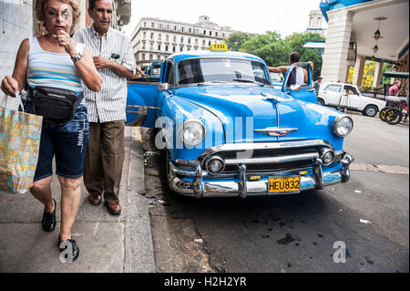 HAVANA - JUNE 12, 2011: Cubans pass a classic American car share taxi waiting for customers with open doors on the - Stock Photo