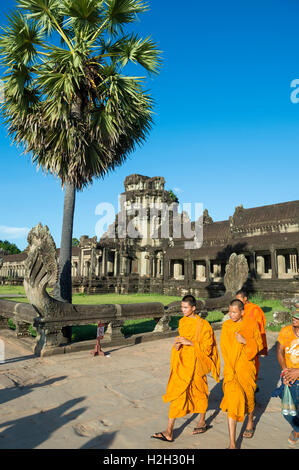 SIEM REAP, CAMBODIA - OCTOBER 30, 2014: Novice Buddhist monks in saffron orange robes pass in front of Angkor Wat. - Stock Photo
