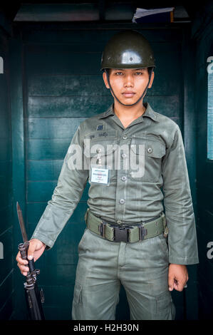 BANGKOK - OCTOBER 26, 2014: Young Thai Army soldier stands guard outside the Grand Palace. Royal Guards serve the - Stock Photo
