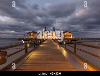 Illuminated historic pier at Ostseebad Sellin, Ruegen, Germany, at night, long exposure - Stock Photo