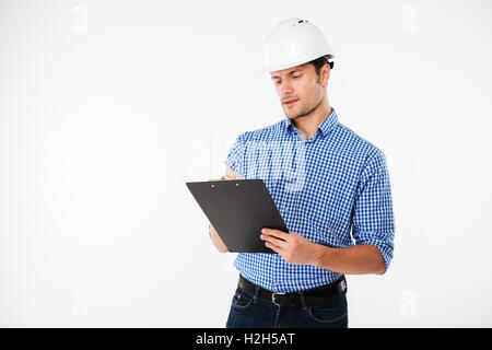 Concentrated young man builder in building helmet writing on clipboard - Stock Photo