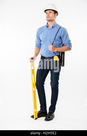 Pensive young man architect in building helmet holding spirit level and thinking - Stock Photo