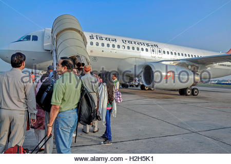 Passengers at Indira Gandhi International Airport, New Delhi boarding Indian Airlines domestic flight in the morning - Stock Photo