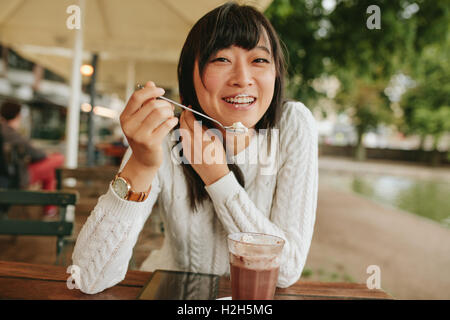 Shot of happy young woman at outdoor cafe eating cold dessert of ice cream. Chinese female enjoying dessert at coffee - Stock Photo