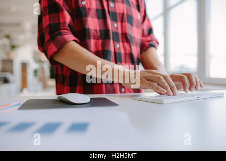 Close up of man hands typing on computer keyboard. Cropped shot businessman working on computer while standing at - Stock Photo