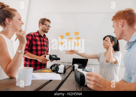 Shot of group of diverse business people discussing virtual reality technology in meeting room. Developers brainstorming - Stock Photo