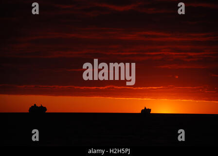 Ship and ships driving on a sea that is completely black, driving in to a red magical sunset. The most beautiful - Stock Photo