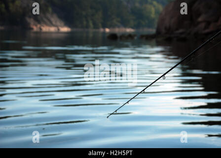 fishing with a fishing rod for salmon and pike in finland in the baltic sea - Stock Photo