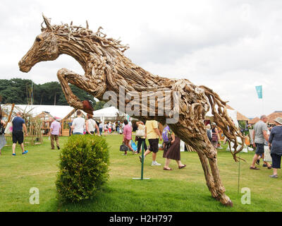 Wooden jumping horse sculpture by James Doran-Webb, for sale at the Tatton Park Flower Show at Knutsford, Cheshire, - Stock Photo