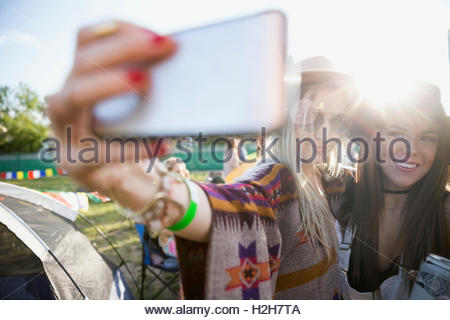 Young women taking selfie at summer music festival campsite - Stock Photo