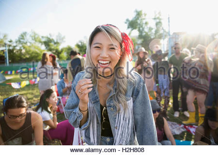 Portrait laughing young woman at summer music festival campsite - Stock Photo