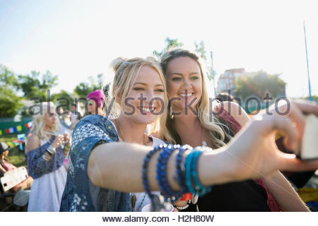 Smiling young women taking selfie at summer music festival campsite - Stock Photo