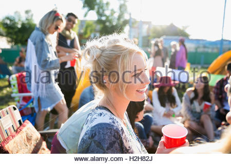 Smiling young woman drinking and hanging out at summer music festival campsite - Stock Photo