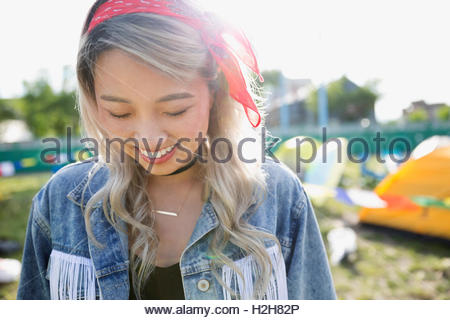 Portrait smiling young woman looking down at summer music festival campsite - Stock Photo