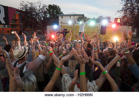 Crowd cheering musician on illuminated stage at summer music festival - Stock Photo