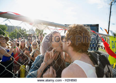 Young couple kissing through chainlink fence at summer music concert - Stock Photo