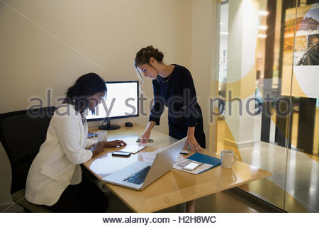 Businesswomen using digital tablet in conference room - Stock Photo