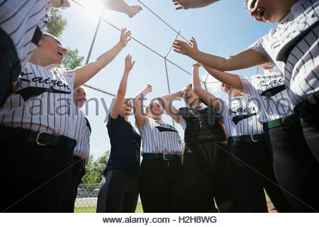 Coach and middle school girl softball team touching hands ...