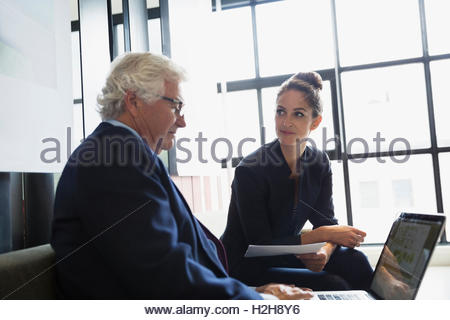 Business people with paperwork working at laptop in office - Stock Photo