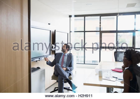 Business people using television in conference room meeting - Stock Photo