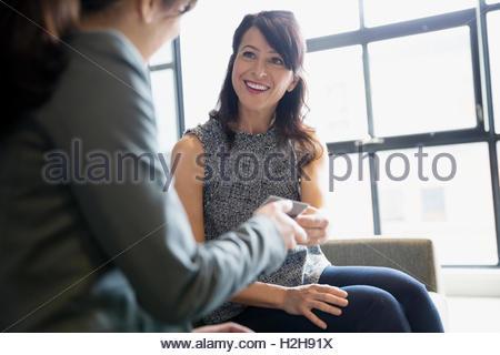 Smiling businesswomen talking in office - Stock Photo