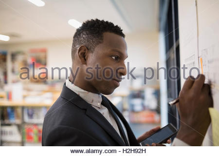 Architect with cell phone editing blueprints hanging on office board - Stock Photo