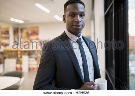Portrait confident businessman drinking coffee in office - Stock Photo