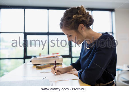 Focused female architect working at table in office - Stock Photo