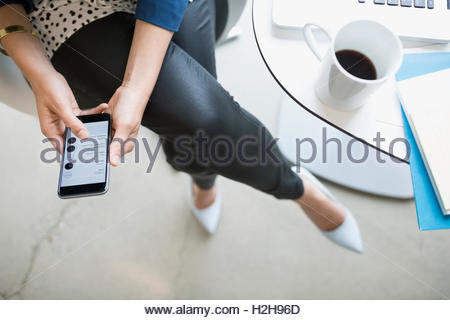 Overhead view businesswoman with coffee using cell phone - Stock Photo