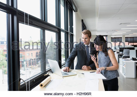Architects working with blueprints at laptop in office - Stock Photo