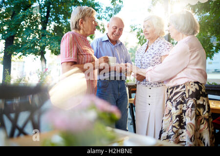 Group of smart seniors interacting at leisure - Stock Photo