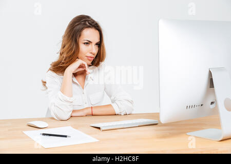 Pensive businesswoman thinking about something and looking at laptop at the office - Stock Photo