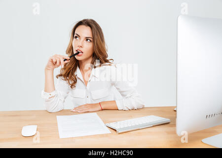 Pensive young businesswoman sitting at the office desk and thinking about something with pen in her mouth - Stock Photo