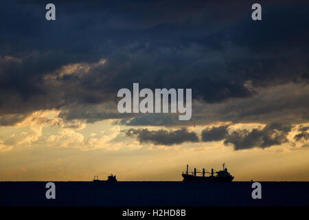 Cargo ships on sea in the rays of the setting sun and dramatic clouds - Stock Photo