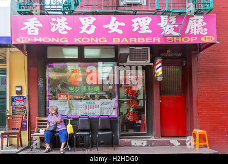 Men getting haircuts on Doyers Street in Chinatown Barber Shop in New York City. - Stock Photo