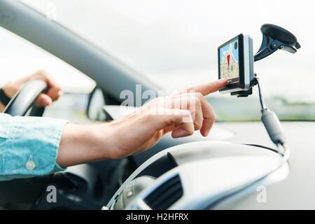 close up of man with gps navigator driving car - Stock Photo