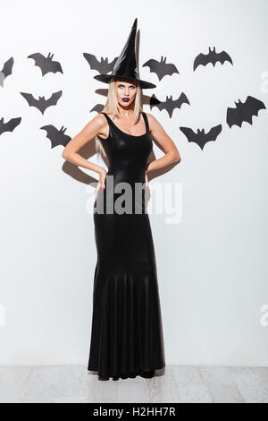 Full length of attractive young woman in black witch costume with hat standing over white background - Stock Photo