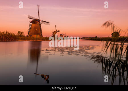 Windmills of Kinderdijk near Rotterdam in Netherlands. Colorful spring scene in the famous Kinderdijk canals with - Stock Photo
