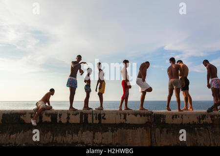 Kids in their bathing suits standing along the seawall about to go swimming along the Malecón in Central Havana, - Stock Photo