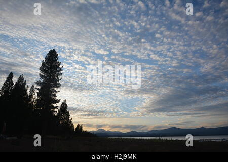 Dramatic, dotted clouds at sunset over Lake Almanor, with Cascade Mountain Range in background - Stock Photo