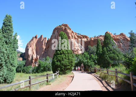 People hiking at Garden of the Gods Park amid sandstone formations and evergreen trees. - Stock Photo
