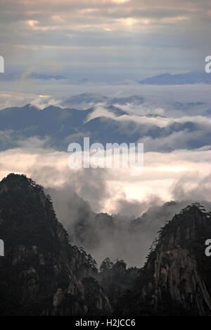 Early morning sun illuminates the sea of clouds floating over the Huangshan mountains. - Stock Photo