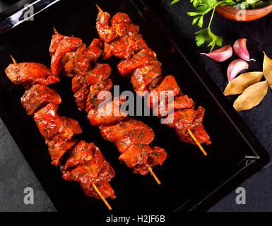 Still life beef skewers over black background - Stock Photo