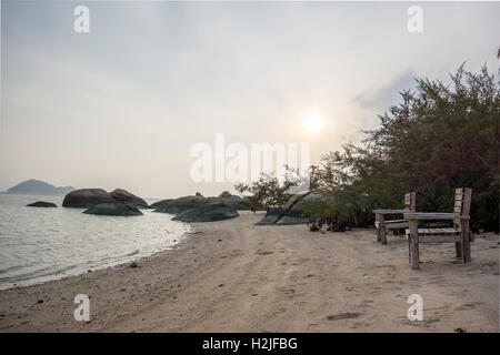 An HDR photo of two empty chairs on a deserted beach in the grey and brown sunset at Koh Pangan, Thailand - Stock Photo