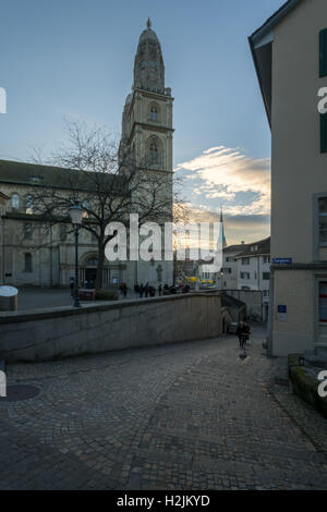 ZURICH, SWITZERLAND - DECEMBER 24, 2015: Sunset view of the Grossmunster (great minster) Church, with locals and - Stock Photo