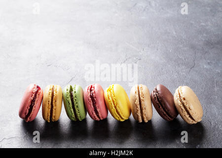 Colorful macaroons on stone table. Sweet macarons. View with copy space for your text - Stock Photo