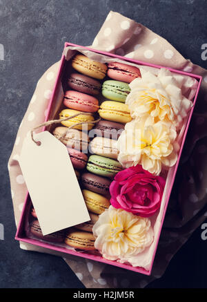 Colorful macaroons and flowers on stone table. Sweet macarons in gift box. Top view. Toned - Stock Photo