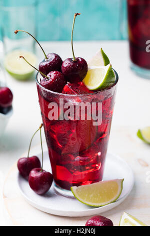Cherry Limeade, lemonade, cola, cocktail in a tall glass on white, turquoise background Copy space - Stock Photo