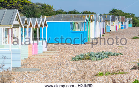 Row of old multicoloured beach huts on a shingle beach in Rustington, West Sussex, England, UK. - Stock Photo