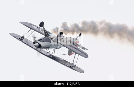 Biplane upside down practicing for an air display. Aircraft is G-J111 single seater single propeller biplane. - Stock Photo